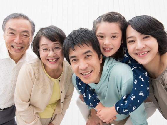 笑顔でこちらを向く三世代家族