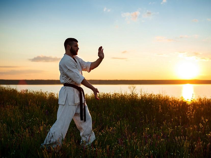 夕日を浴びて空手の練習をする男性