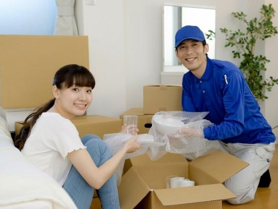 引越し作業員と荷物を整理する女性