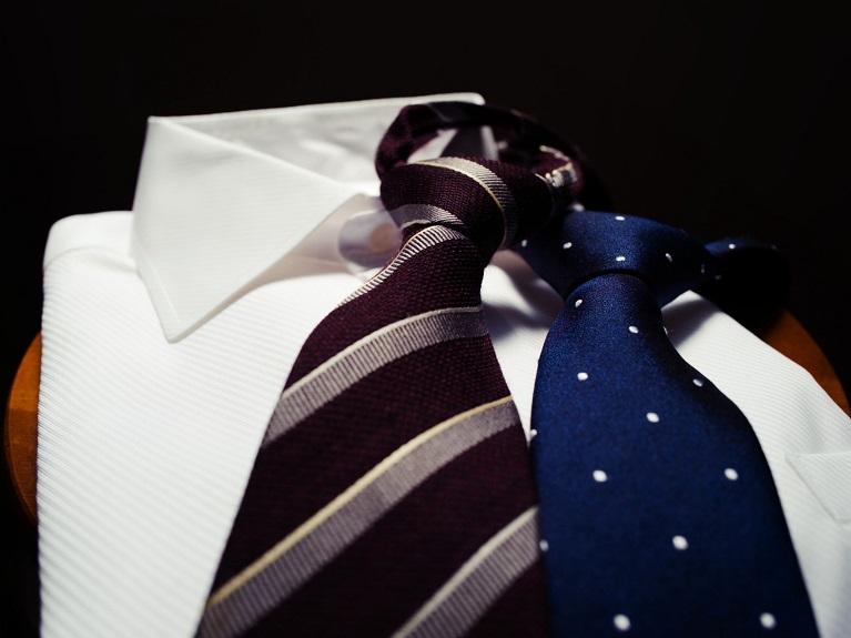 白いワイシャツと黒とグレーの縞模様とブルーのドット柄のネクタイ
