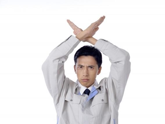 両手を交差させてNGを表す作業着の男性