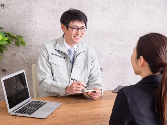 笑顔の男性作業員に相談を受ける女性