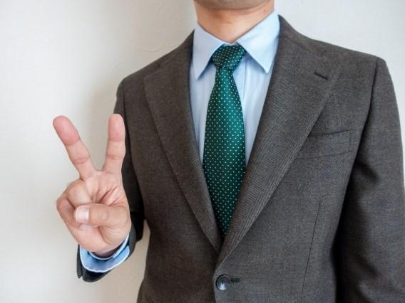 2本指を立てる男性
