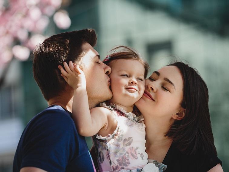 父と母からキスをされる幼女