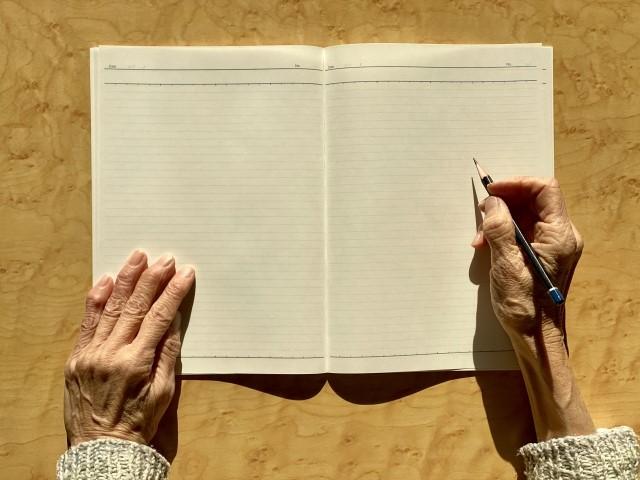 ノートを書く高齢者の手
