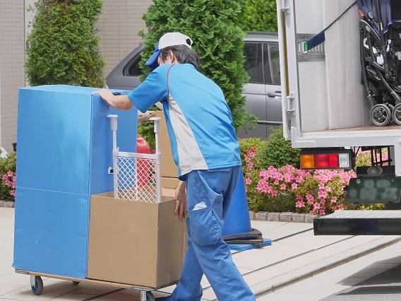 トラックから荷物を下ろし荷台に積んで運ぶ引越しスタッフ