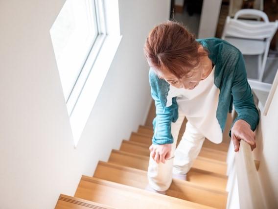 手すりを持って歩く女性