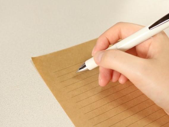 茶色い用紙に字を書く手