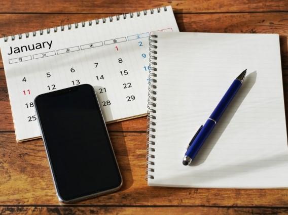 木目机に置かれたカレンダーとスマホとノート