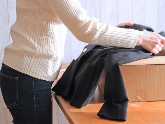 灰色のコートを畳む女性