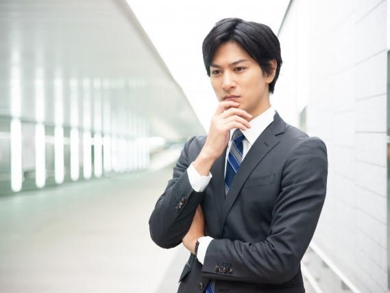 考え事をする若いビジネスマン