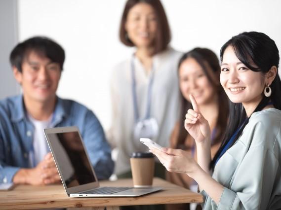 PCとスマホを使ってミーティングをしている若いグループ