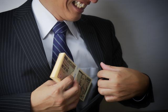 懐に大金を入れ笑みを浮かべるスーツ男性