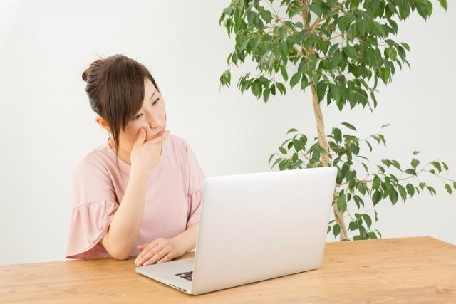 """パソコンの前で悩む女性"""""""